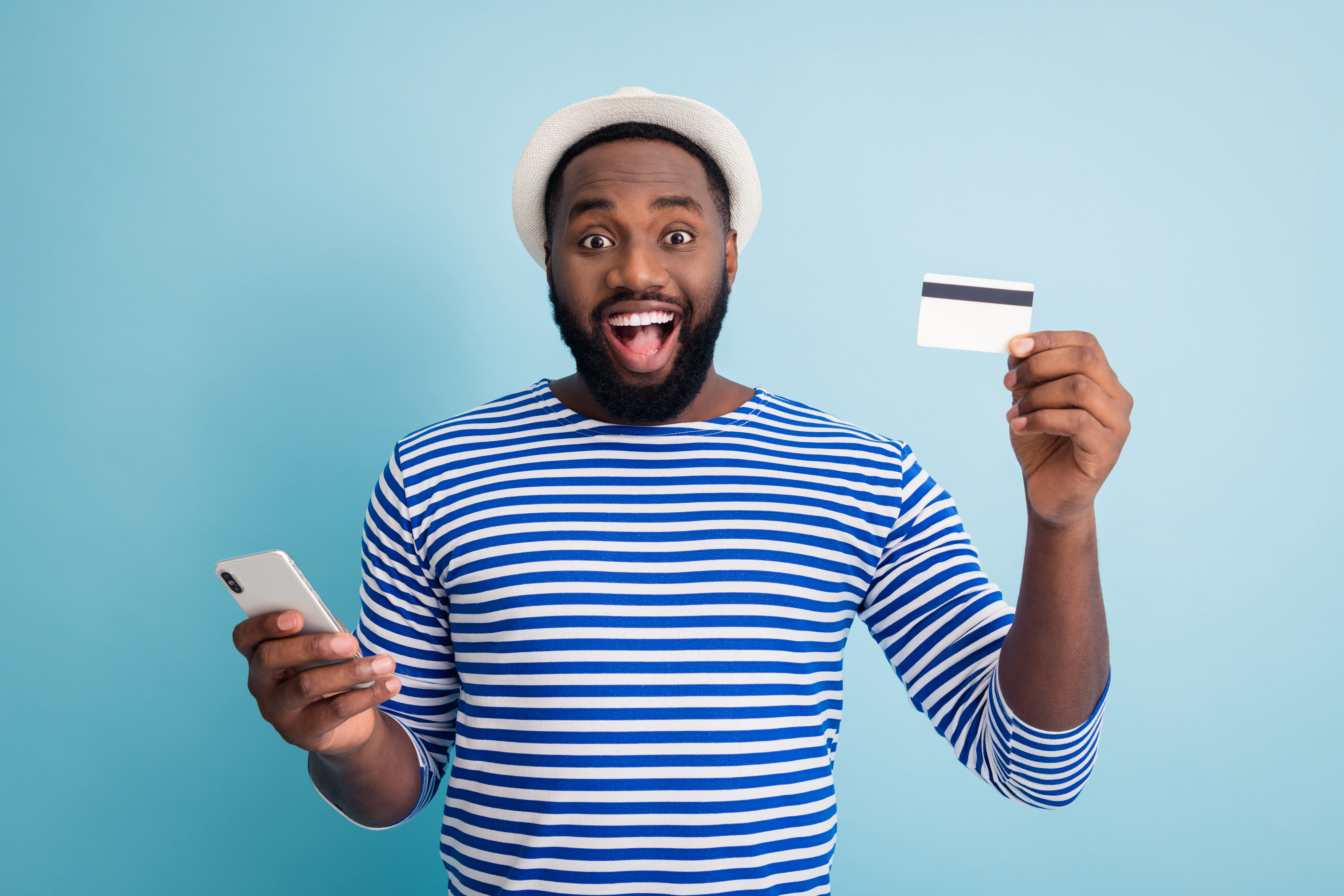 2021/photo-funny-dark-skin-guy-hold-telephone-app-browsing-making-online-purchase-use-cool-service-credit-card-wear-white-sun-cap-striped-sailor-shirt-isolated-blue-color-wall.jpeg